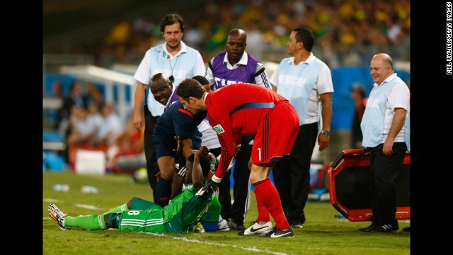 Goalkeeper Asmir Begovic of Bosnia-Herzegovina assists Michael Babatunde of Nigeria off the field.