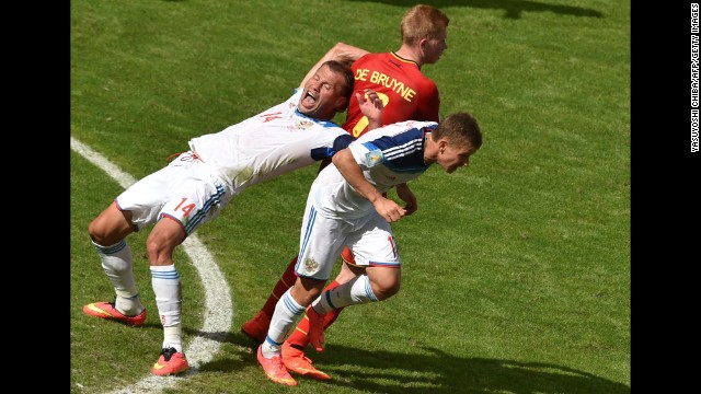 Belgium's midfielder Kevin De Bruyne is challenged by Russia's defender Vasily Berezutskiy, left, and midfielder Oleg Shatov.