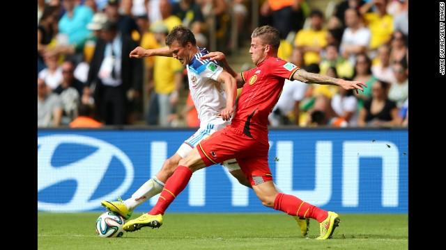 Toby Alderweireld of Belgium challenges Maksim Kanunnikov of Russia.