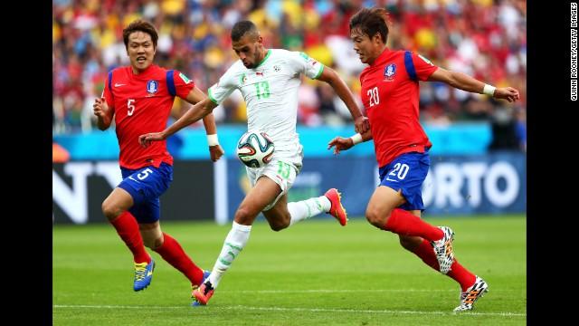 Islam Slimani of Algeria breaks through South Korean defenses on his way to scoring his team's first goal.