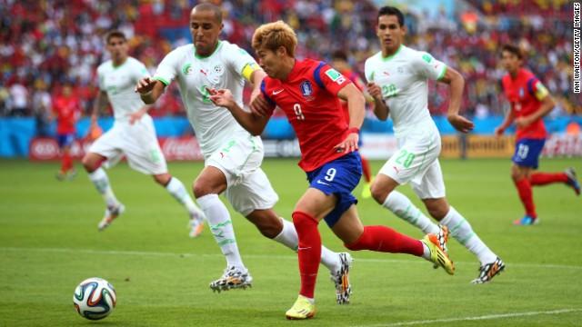 Son Heung-min of South Korea controls the ball against Madjid Bougherra of Algeria.