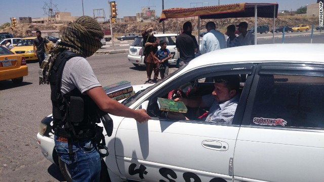 An ISIS member distributes a copy of the Quran, Islam's holy book, to a driver in Mosul on June 22.