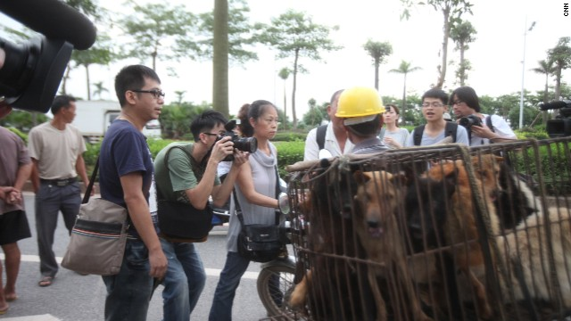 Activists block a dog trader's motorcycle to prevent him from leaving.