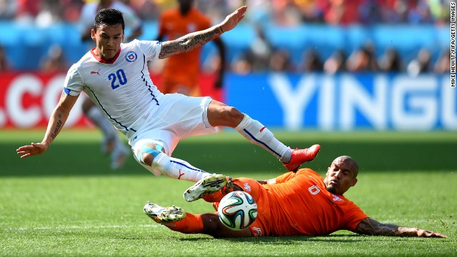 Charles Aranguiz of Chile is tackled by Nigel de Jong of the Netherlands.