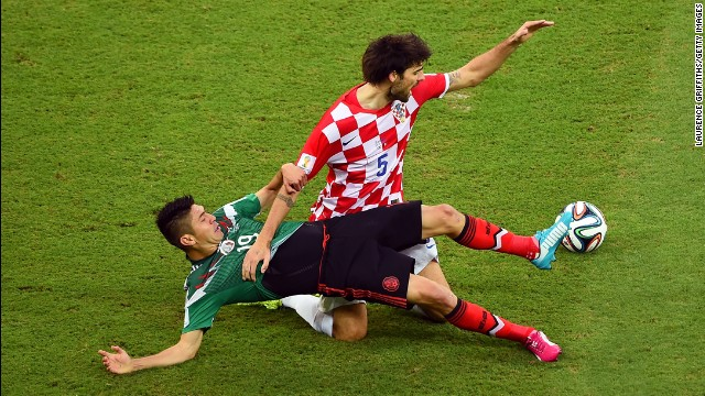 Oribe Peralta, left, of Mexico tackles Vedran Corluka of Croatia.