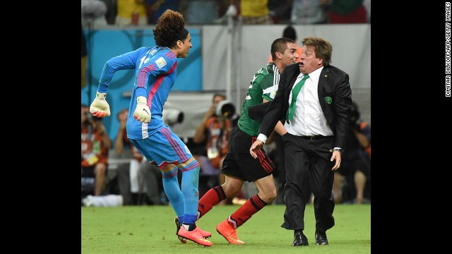 Mexican goalkeeper Guillermo Ochoa, left, and coach Miguel Herrera celebrate a goal by their team during a World Cup match against Croatia on Monday, June 23, in Recife, Brazil. Mexico won 3-1.