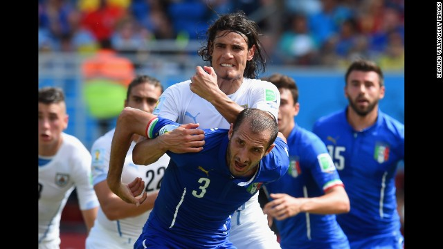 Giorgio Chiellini of Italy and Edinson Cavani of Uruguay tussle.