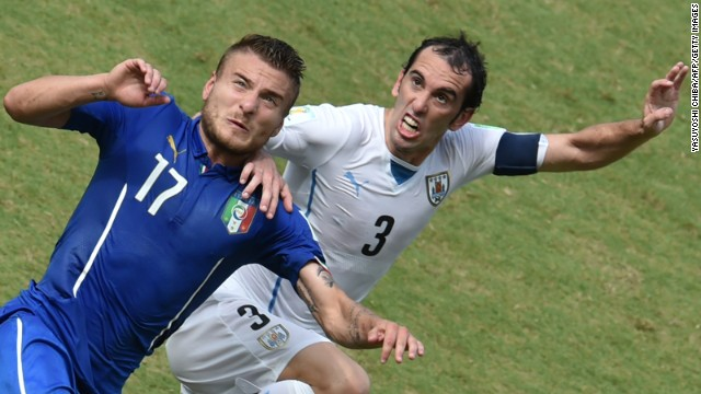 Italy forward Ciro Immobile, left, vies with Uruguay defender Diego Godin.