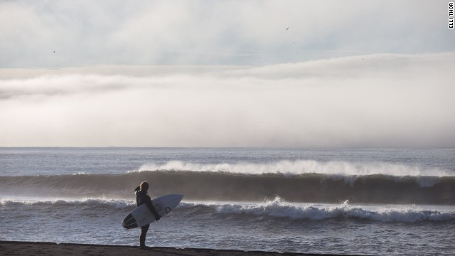 Surfing around Reykjanes, Iceland, presents various challenges, not least the freezing temperatures, making wetsuits and foot protection essential.