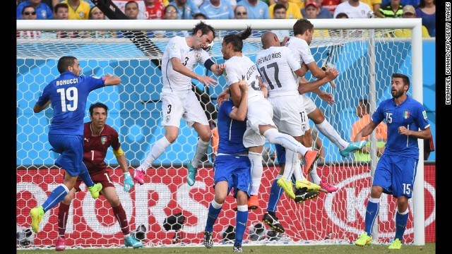 Uruguay defender Diego Godin, third left, scores.