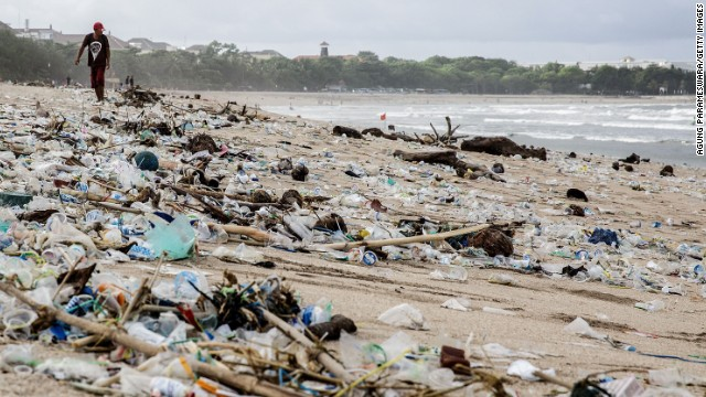 A man walks beside the scattered plastic trash brought in by waves at Kuta Beach in Indonesia in January 2014.