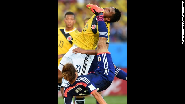 Japan's Yoshito Okubo, bottom, and Colombia's Carlos Valdes vie for the ball.