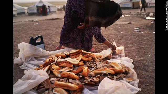 A woman gathers bread in a temporary displacement camp for Iraqis on Tuesday, June 24.