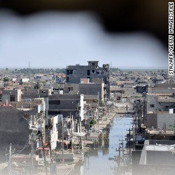 A picture taken through a hole in a wall on June 24, 2014 in the city of Ramadi in the Anbar province, shows buildings that were damaged during fightings between government forces including fighters of the Sunni anti-Al-Qaeda militia Sahwa (Awakening) and anti-government militants, including from the jihadist Islamic State of Iraq and the Levant (ISIL).