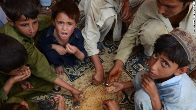 Hungry Pakistani children eat rice together on their arrival in Bannu.