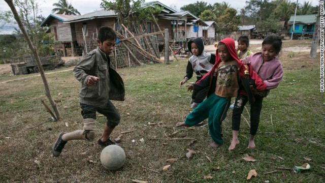 One of the land mine victims photographer Paula Bronstein met in Laos was a 10-year-old named Aiyaok. He is seen here playing soccer with other children in the village of Tamluang.