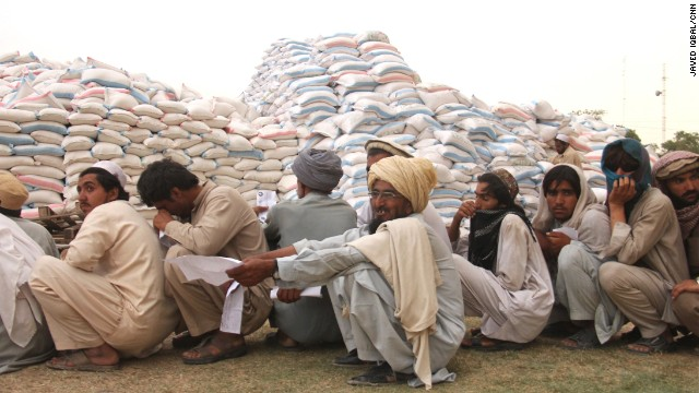 Sacks of wheat are heaped in mounds in the center of the distribution point.