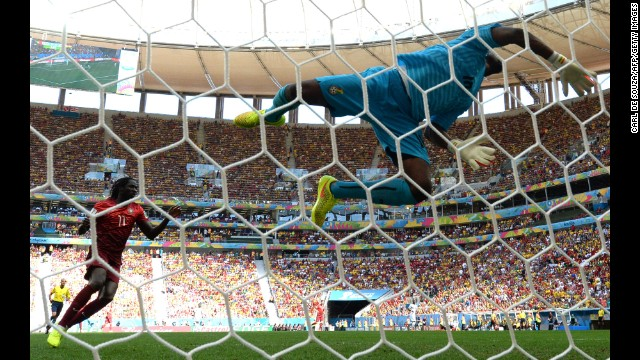 Ghana goalkeeper Fatau Dauda dives for the ball.