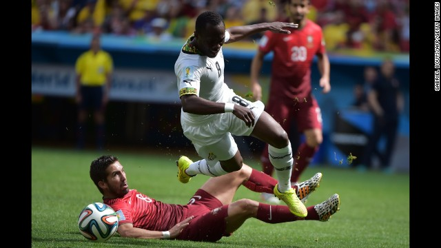 Portugal's Joao Moutinho and Ghana's Emmanuel Agyemang Badu fight for the ball.