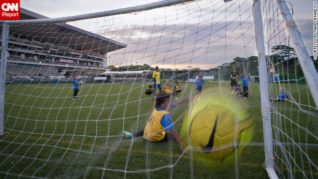"A ball <a href='http://ireport.cnn.com/docs/DOC-1143657'>flies into the net</a> during a youth training session in Singapore. ""Parents hide in the shade while kids run around for hours. Hard to understand how can they t"