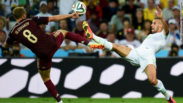 Islam Slimani of Algeria and Denis Glushakov of Russia compete for the ball.