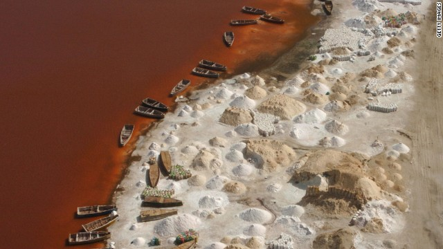 Piles of salt drying on the shores of Lake Retba. The lake's salt content rivals that of the Dead Sea and the combination of the sun and salt-loving micro-algae has given the water its color.