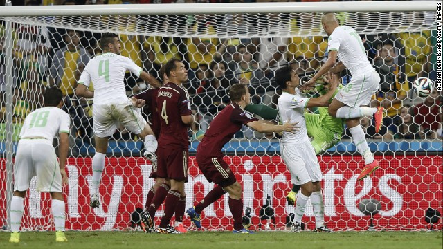 Algeria forward Islam Slimani, right, scores his team's first goal past Russia's goalkeeper Igor Akinfeev.