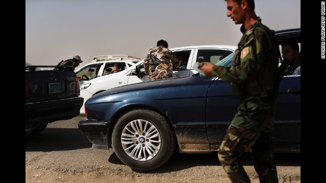 Peshmerga fighters, or Kurdish warriors, check cars at the entrance to a temporary displacement camp in Khazair, Iraq, for people caught in the fighting in and around the city of Mosul on Thursday, June 26.