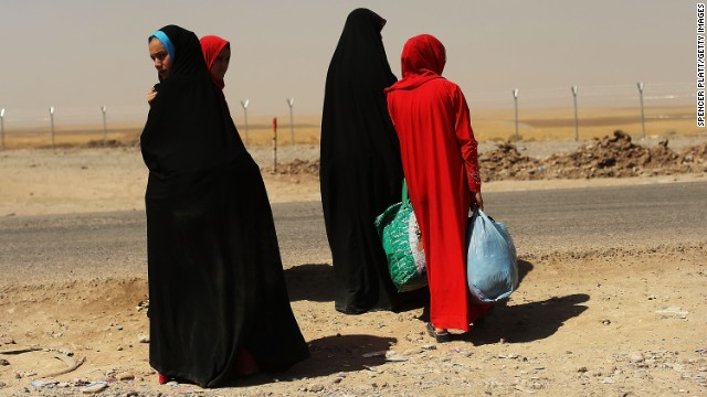 A group of women wait outside the temporary displacement camp in Khazair on June 26.