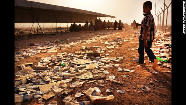 A child walks over discarded water bottles and trash at a registration area in the displacement camp in Khazair on June 26.