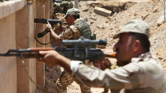 Kurdish Peshmerga take their positions behind a wall on the front line of the conflict with ISIS militants in Tuz Khormato, Iraq, on Wednesday, June 25.