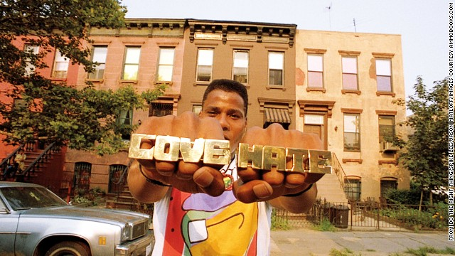 """Radio Raheem wears """"love"""" and """"hate"""" on his rings, a reflection of the neighborhood's volatility (and a nod to Robert Mitchum's preacher character in """"Night of the Hunter,"""" who has the words tattooed on his knuckles). Another character, a mentally challenged man named Smiley, sells pictures of Malcolm X and the Rev. Martin Luther King Jr., another symbol of duality."""