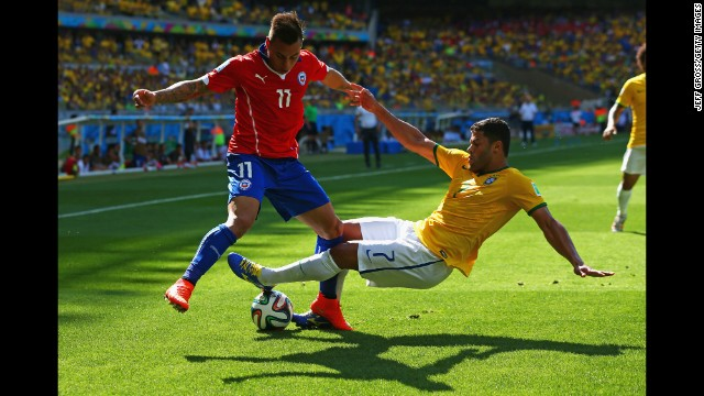 Hulk of Brazil tackles Eduardo Vargas of Chile.