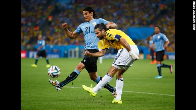 Edinson Cavani of Uruguay, left, challenges Mario Yepes of Colombia.