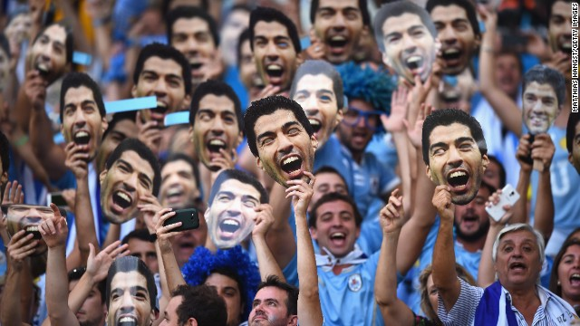 Uruguay fans hold up Luis Suarez masks before the game between Uruguay and Colombia. Suarez was banned from nine matches and four months of soccer-related activity after he bit an opponent in Uruguay's previous game.