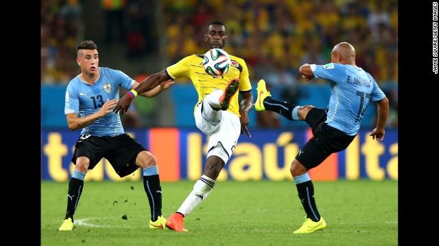 Jackson Martinez of Colombia controls the ball against Jose Gimenez, left, and Egidio Arevalo Rios of Uruguay.