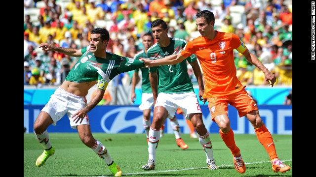 Netherlands forward Robin van Persie pulls the jersey of Mexico's captain Rafael Marquez.