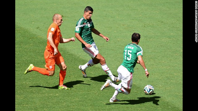 Arjen Robben of the Netherlands vies for the ball with Francisco Rodriguez, center, and Hector Moreno of Mexico.