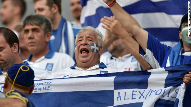 Greek fans cheer before the start of the game.