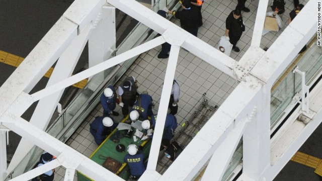 Japanese firefighters and investigators work at the scene of a self-immolation in Tokyo on Sunday, June 29, 2014.