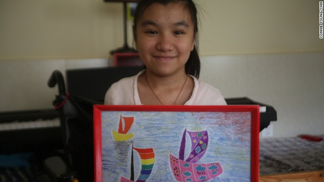 A girl at Agape Family Life House foster home near Tianjin displays a picture she has painted. She raises money by selling her paintings. The foster home specializes in caring for orphaned children and young adults with brittle bone disease.