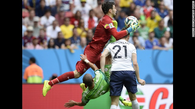 French goalkeeper Hugo Lloris collects the ball as Odemwingie attempts to score during the first half.