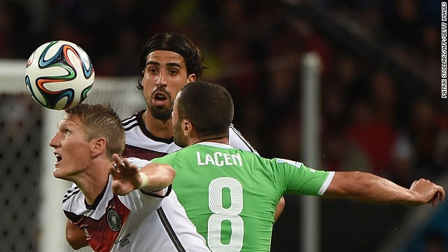 Germany's Bastian Schweinsteiger, left, and Sami Khedira fight for the ball with Algeria midfielder Medhi Lacen.