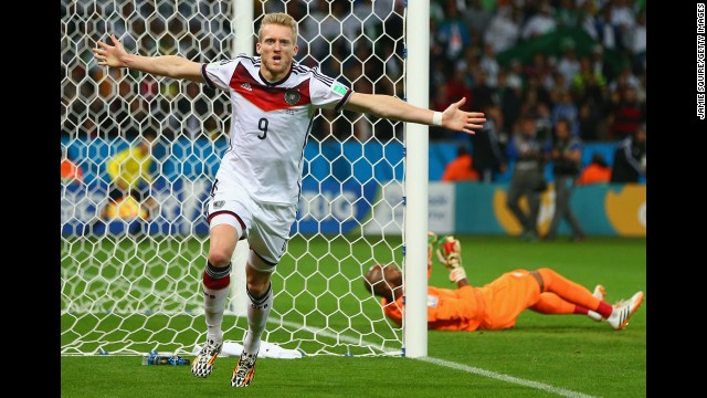 Andre Schuerrle of Germany celebrates scoring his team's first goal past goalkeeper M'Bolhi of Algeria.
