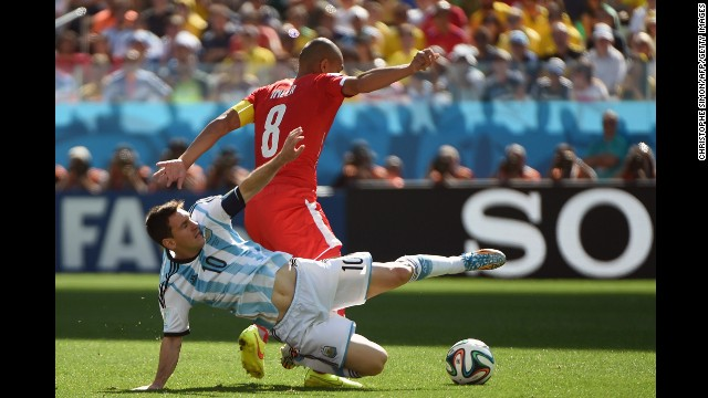 Messi and Swiss midfielder Goekhan Inler fight for the ball.