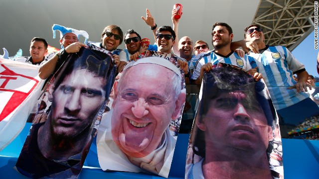 Argentina fans celebrate before the match. The faces, from left to right, are three of the world's most famous Argentines: Messi, Pope Francis and soccer legend Diego Maradona.