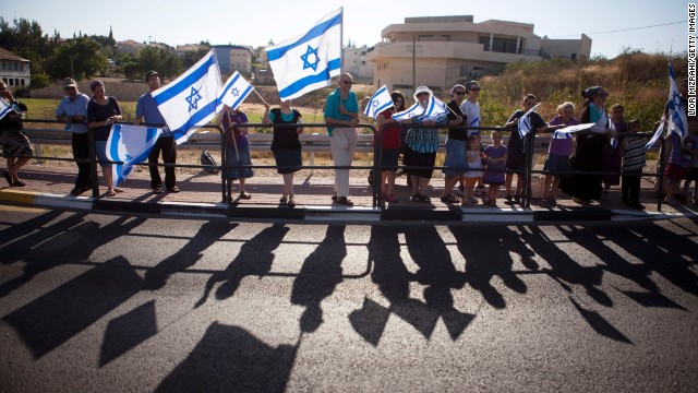 People hold Israeli flags during Shaar's funeral procession in Hashmonaim, West Bank.