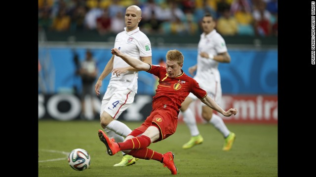Bradley, left, looks on as De Bruyne kicks the ball.