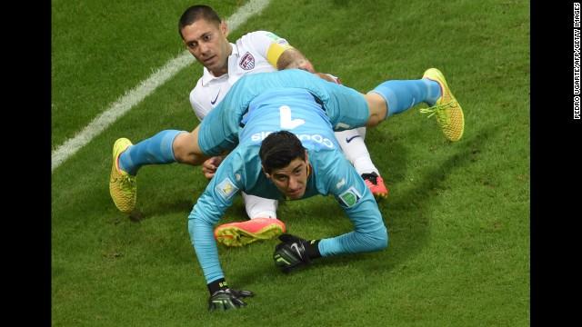 Belgium's goalkeeper, Thibaut Courtois, falls on U.S. forward Clint Dempsey.