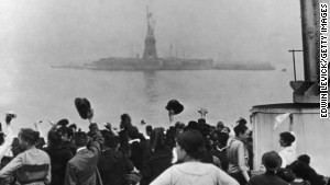 Immigrants traveling aboard a ship celebrate as they catch their first glimpse of the Statue of Liberty and Ellis Island in New York Harbor in 1915.